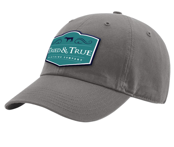Our very own unstructured old fashion hat. All Charcoal and a Badge style teal patch, containing Tried & True in the middle with a pointer silhouette above.