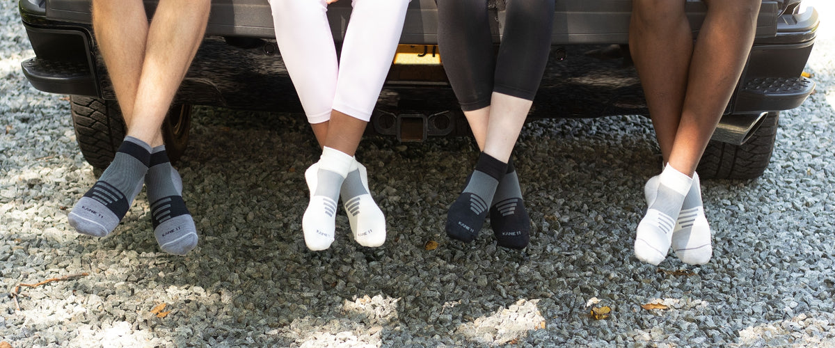 Four pairs of feet in socks sitting on truck tailgate.
