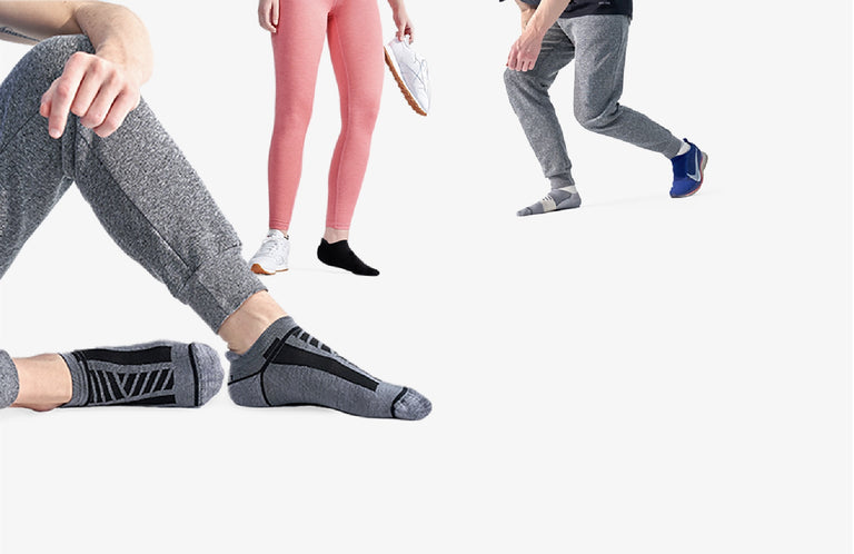 Two men in athletic pants and ankle socks. One women in athletic tights and ankle socks.