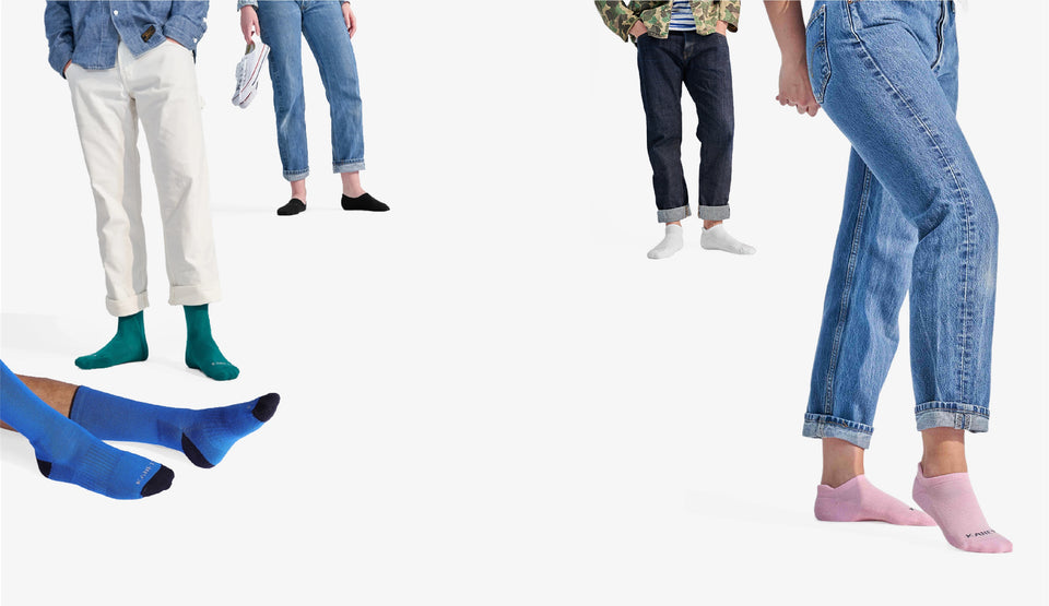Three people waist down in jeans and ankle socks. One person in white pants and green socks. One person with blue crew socks.