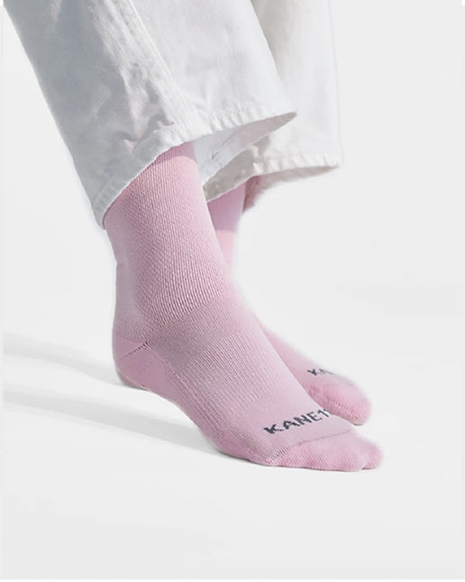 Women in white pants and pink crew socks on white background.