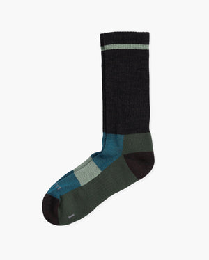 Mens wool crew sock in: brown with green and teal. Laid flat.