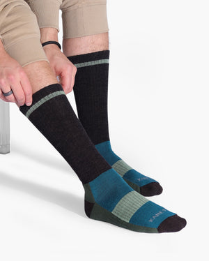 Mens wool crew sock in: brown with green and teal. Lifestyle.