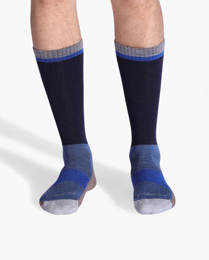 Mens wool crew sock in: navy with brown and blue. On feet.