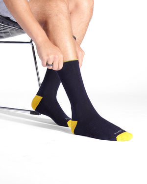 Mens navy sock with yellow caps, crew height, lifestyle image.