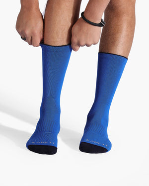 Mens royal blue sock with black caps, crew height, on feet.