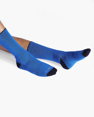 Mens royal blue sock with black caps, crew height, lifestyle image.