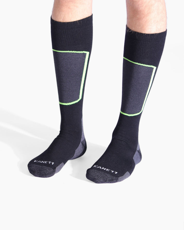 Mens over the calf ski sock in black. Heather black/grey toe, heel cap and shin. Shin outlined in lime green. On feet.