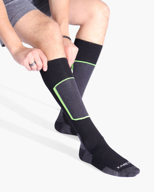 Mens over the calf ski sock in black. Heather black/grey toe, heel cap and shin. Shin outlined in lime green. Lifestyle image.