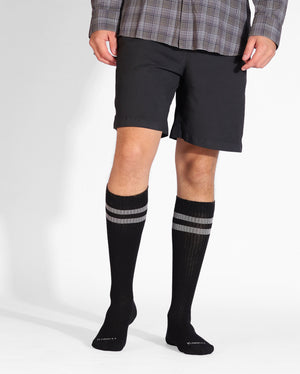 Mens over the calf sock in black with two grey stripes at top, on feet.