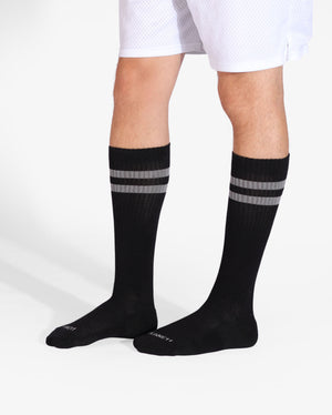 Mens over the calf sock in black with two grey stripes at top, lifestyle image.