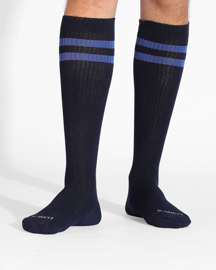 Mens over the calf sock in navy with two royal blue stripes at top, on feet.