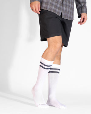 Mens over the calf sock in navy with two royal blue stripes at top, lifestyle image.
