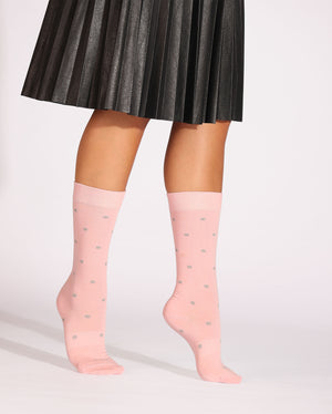 Womens pink sock with grey dots, crew height, lifestyle image.