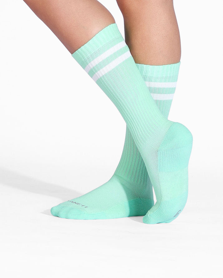 Womens crew sock in mint green with two white stripes at top, on feet.