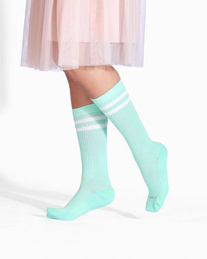 Womens crew sock in mint green with two white stripes at top, lifestyle image.
