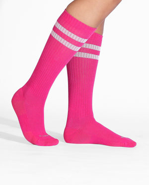 Womens crew sock in pink with two white stripes at top, on feet.