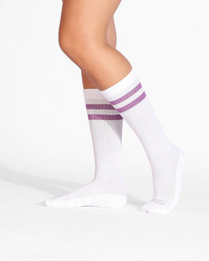 Womens crew sock in white with two purple stripes at top, on feet.