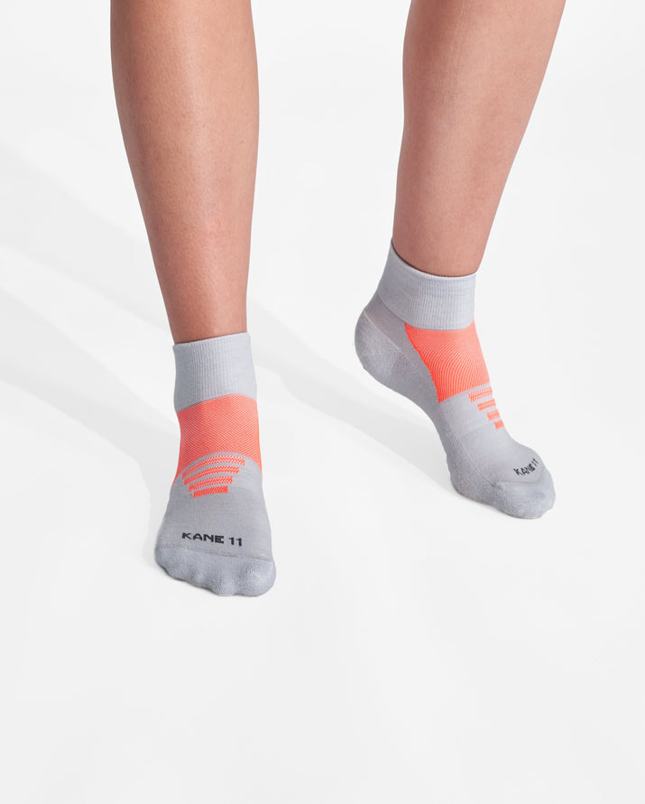womens quarter sock in grey with neon orange on feet