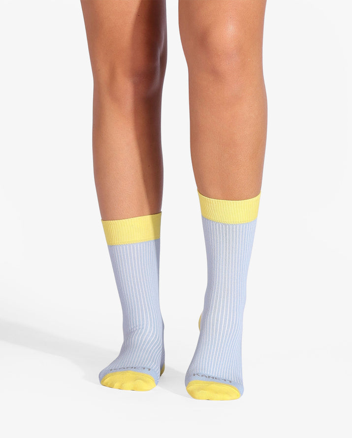 Womens crew sock in blue with yellow heel and toe caps. Yellow cuff and white between the top cuff and the heel. On feet.