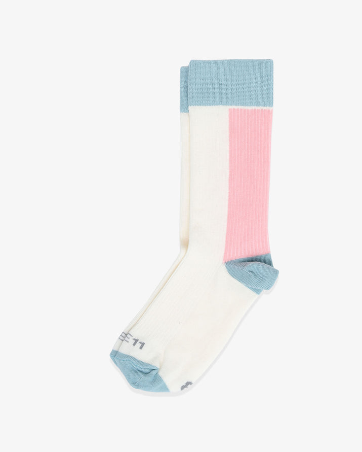Womens crew sock in ivory with blue heel and toe caps. Blue cuff and pink between the top cuff and the heel. Laid flat.