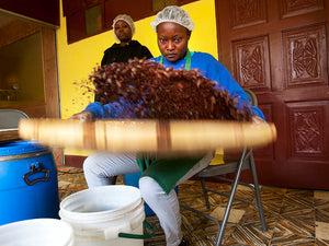 "Two female employees at Askanya Chocolates winnowing cacao beans with a Haitian flat basket called ""laye"""