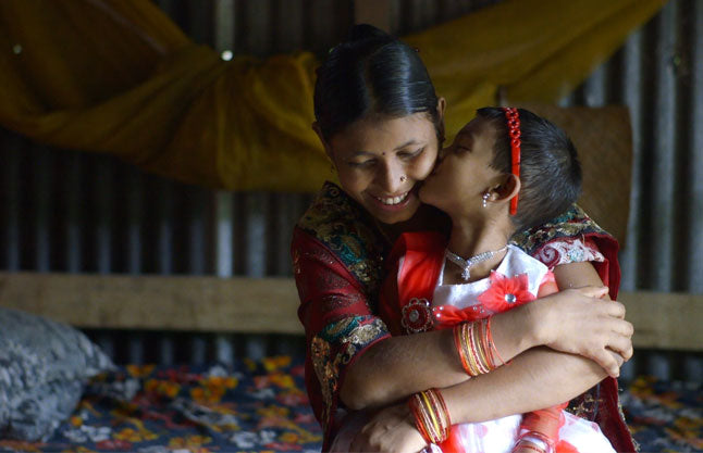 A film still from The True Cost featuring a Bangladeshi garment worker and her daughter.