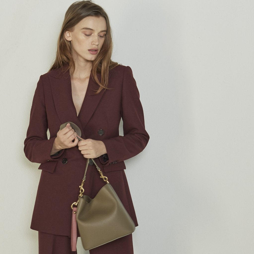 Model in suit with Angela Roi Vegan Angelou Mini Bucket Bag in Brown