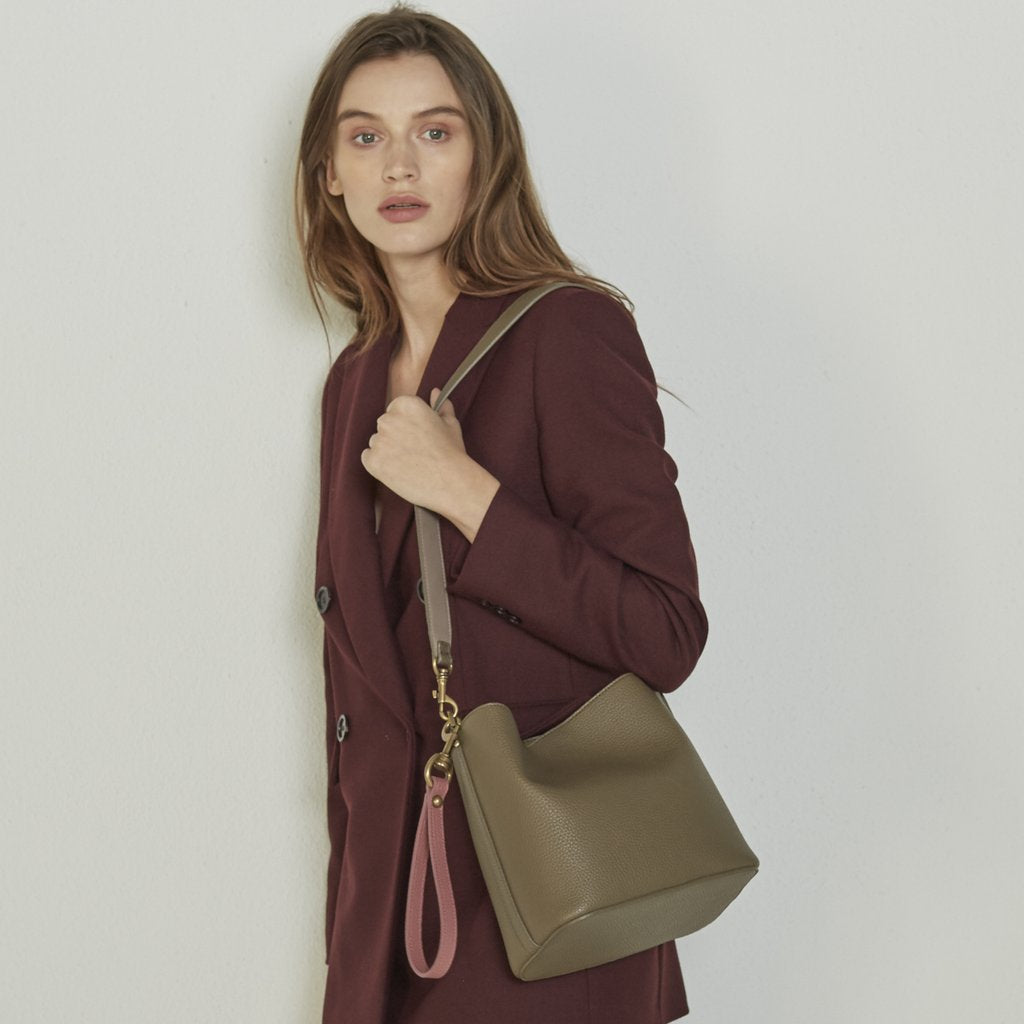 Model in suit with Angela Roi Vegan Angelou Mini Bucket Bagin Brown, with hand and shoulder strap
