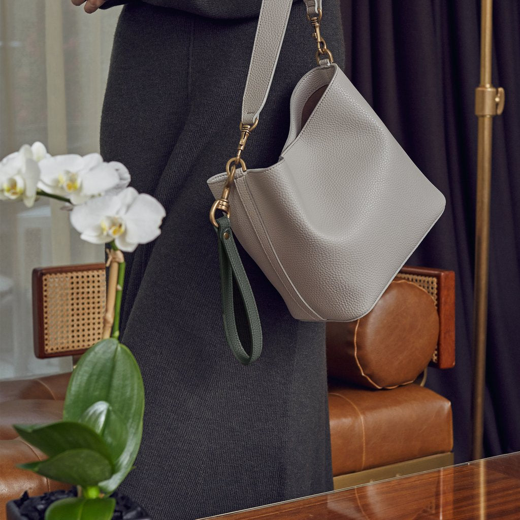 Casual wear with the Angela Roi Vegan Angelou Mini Bucket Bag in Light Gray, Shoulder and Hand Straps