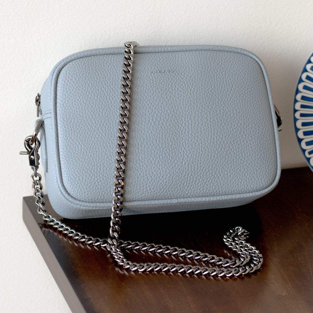 Grace Mini Cross-body in Light Nude Blue on table