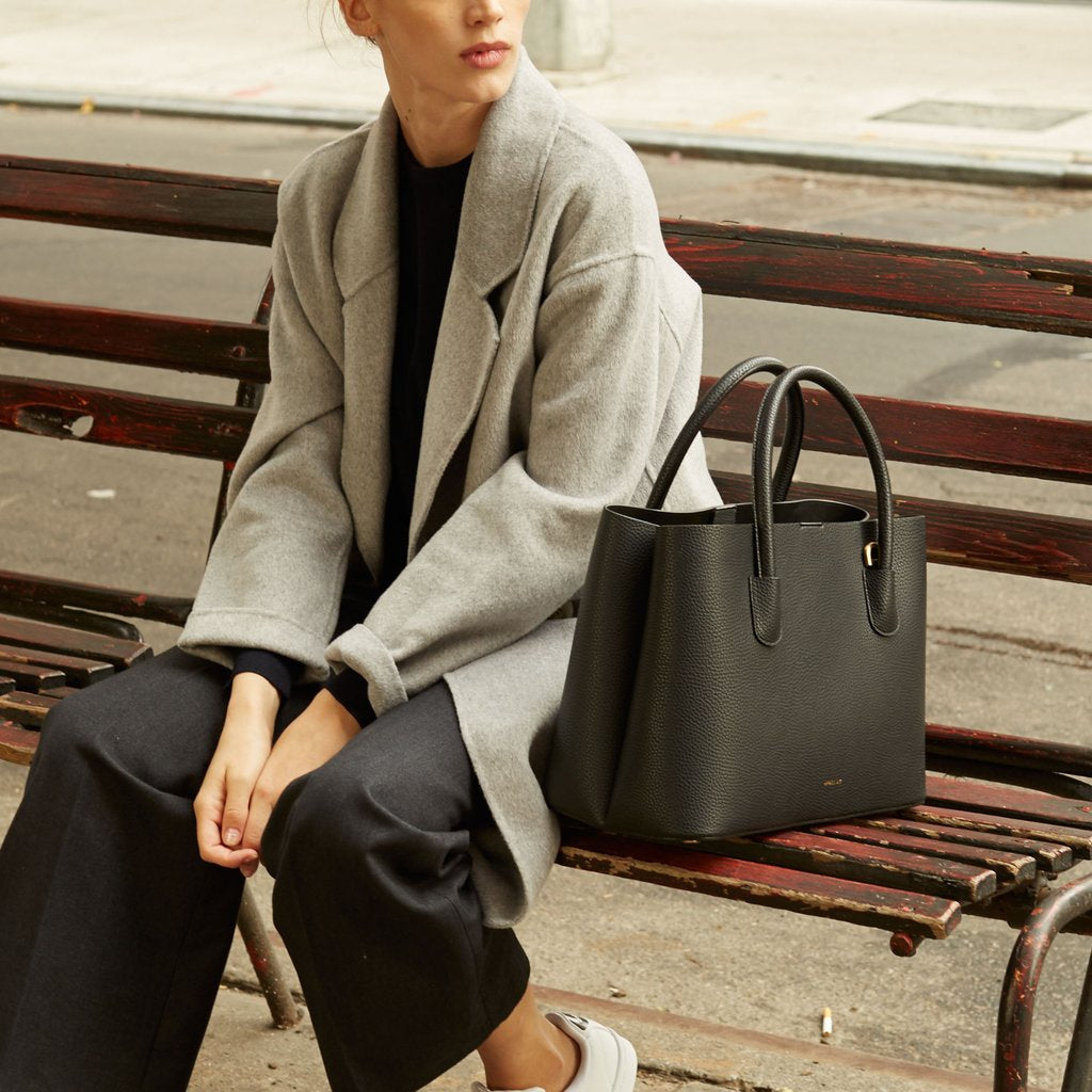 Angela Roi Vegan Cher Tote in Black, with model on bench