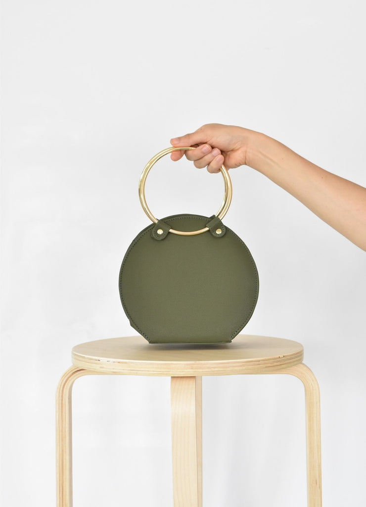 Ceibo Handcrafted Ring Bag in Olive, front view in hand