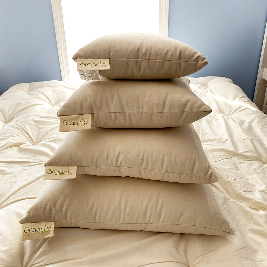 Stack of four natural kapok pillow inserts with organic cotton cover in various sizes.