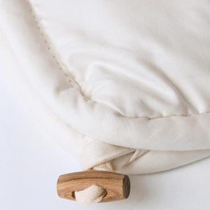 Detail shot of the wooden toggle used to link together multiple organic wool comforters and an organic cotton duvet cover.
