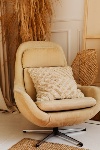 beige chair, pillow, carpet, and decor