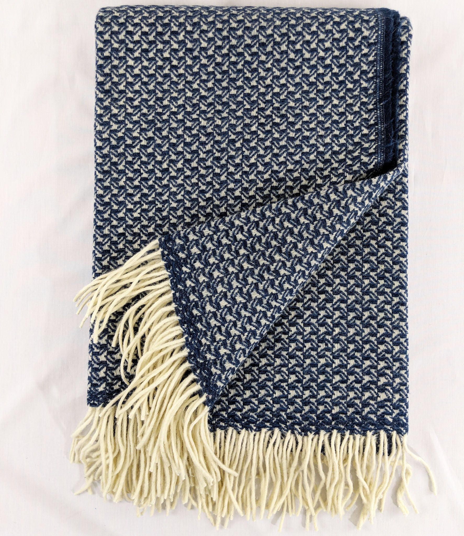 Dark blue Merino wool throw with tight wing pattern and fringe against white background