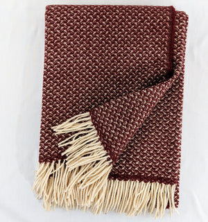 Maroon Merino wool throw with tight wing pattern and fringe against white background