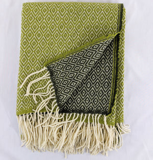 Green and light green Merino throw with double lozenge pattern against white background