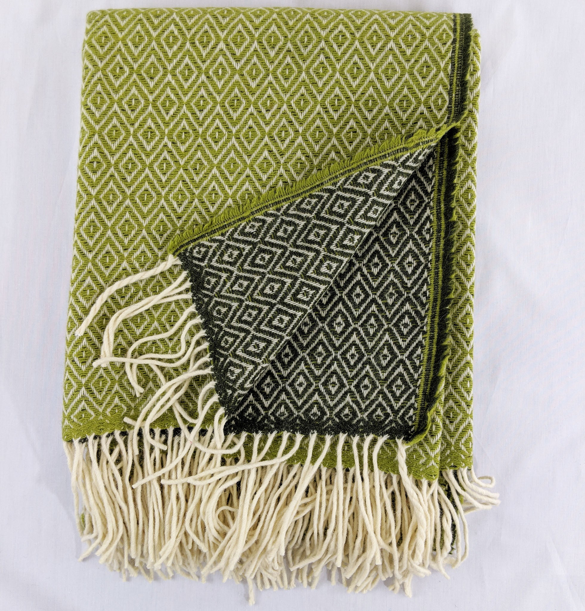 Dark green and light green Merino throw with double lozenge pattern against white background