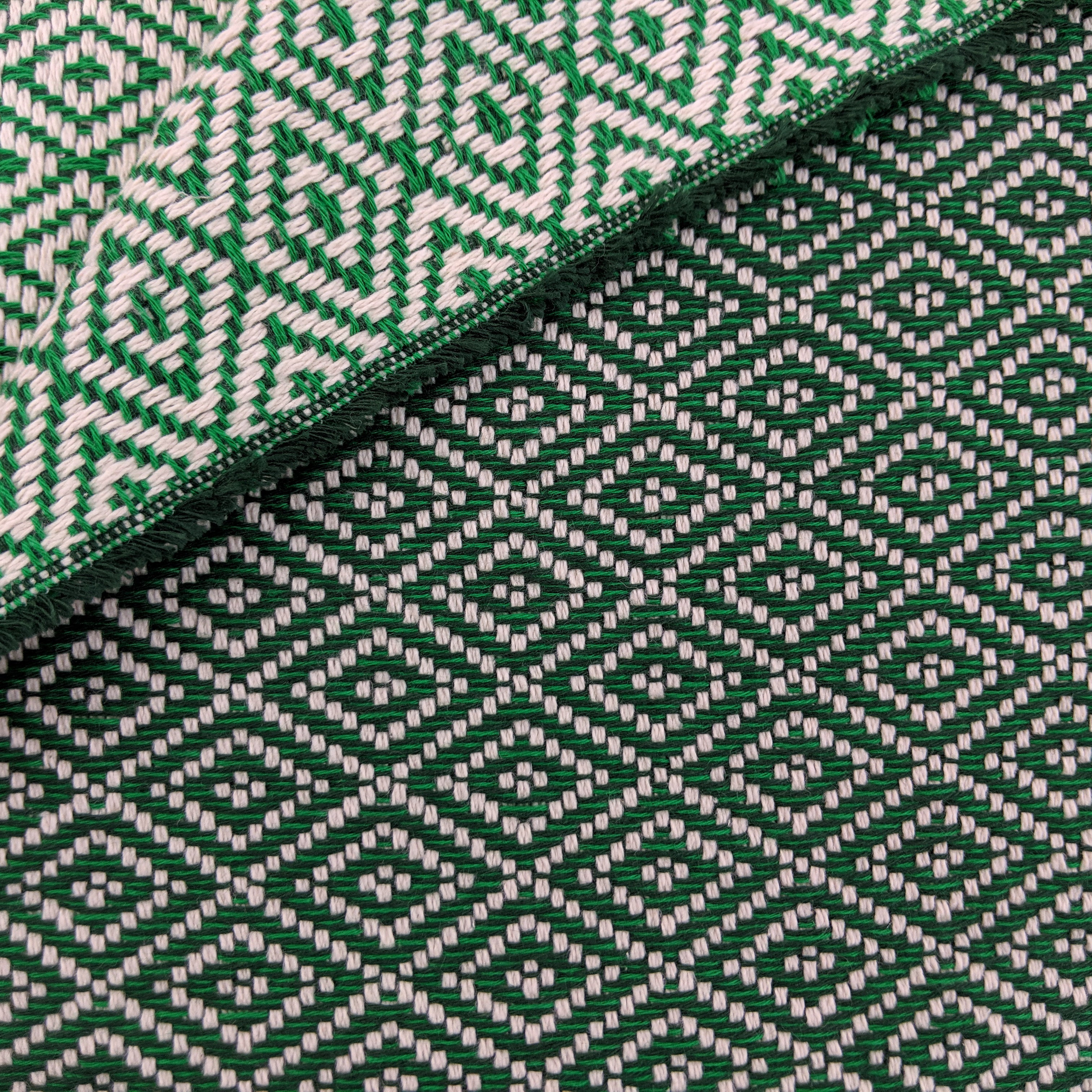 Green and dark green cotton throw with double lozenge pattern, close up
