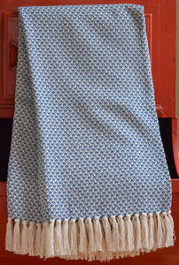 Blue cotton throw in tight wing pattern with fringe folded into table drawer