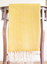 Yellow Merino throw with flower weave pattern folded over a side table