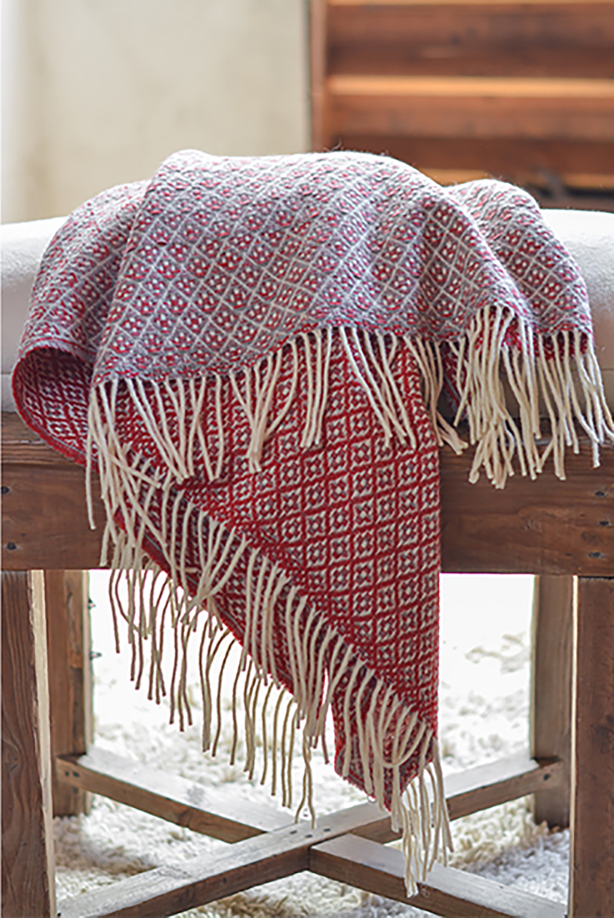 Red and grey Merino throw with flower weave pattern folded over a side table