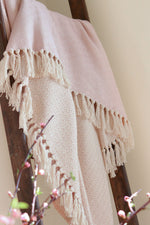 Pink and white cotton throw with double lozenge pattern hanging on a ladder