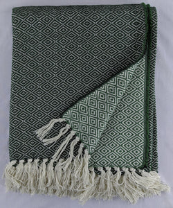 Green and dark green cotton throw with double lozenge pattern against a white background