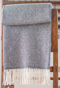Dark gray Merino throw with double lozenge pattern folded over a side table