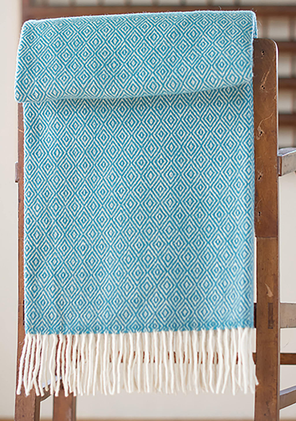 Teal Merino throw with double lozenge pattern folded over a side table