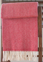 Red Merino throw with double lozenge pattern folded over a side table