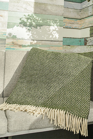 Dry green Merino wool throw with tight wing pattern and fringe folded over sofa